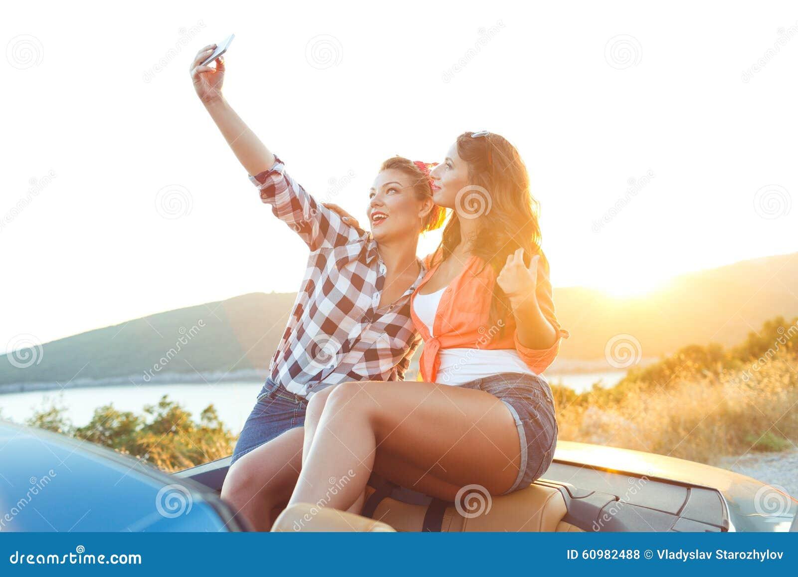 2 молодых красивых девушки делают selfie в автомобиле с откидным верхом