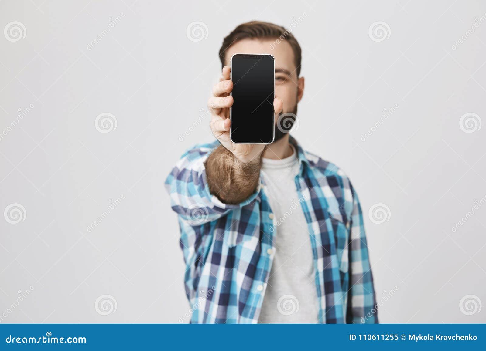 Мужская модель с бородой и ультрамодная стрижка в проверенной рубашке показывая smartphone на стороне заволакивания камеры с ей,