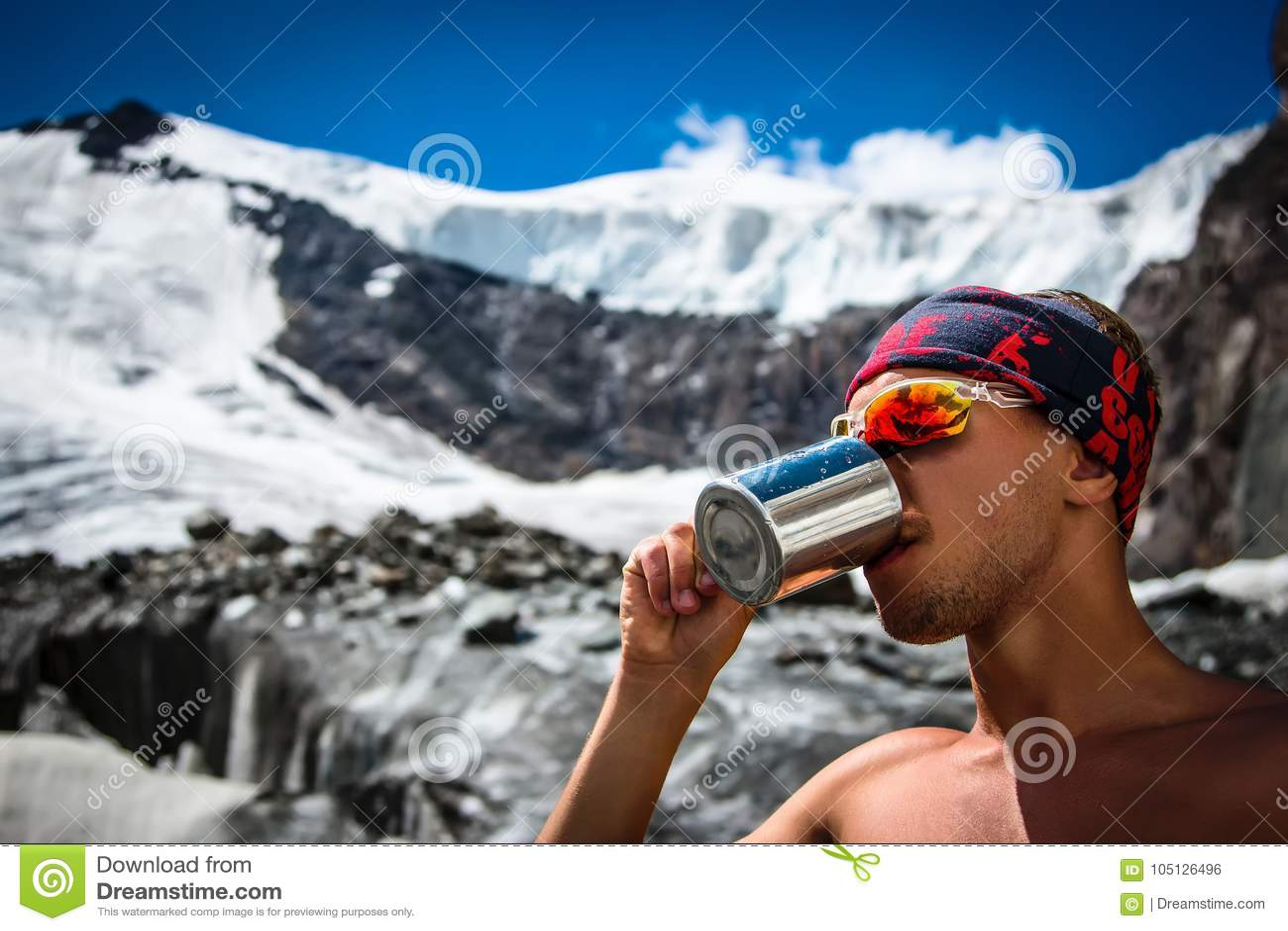 Мужская питьевая вода альпиниста от кружки на леднике в extre каникул active приключения концепции образа жизни перемещения гор