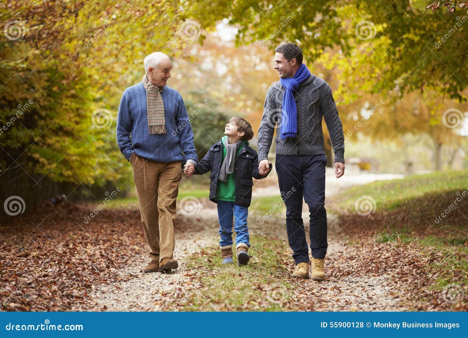 Мужская семья поколения Multl идя вдоль пути осени