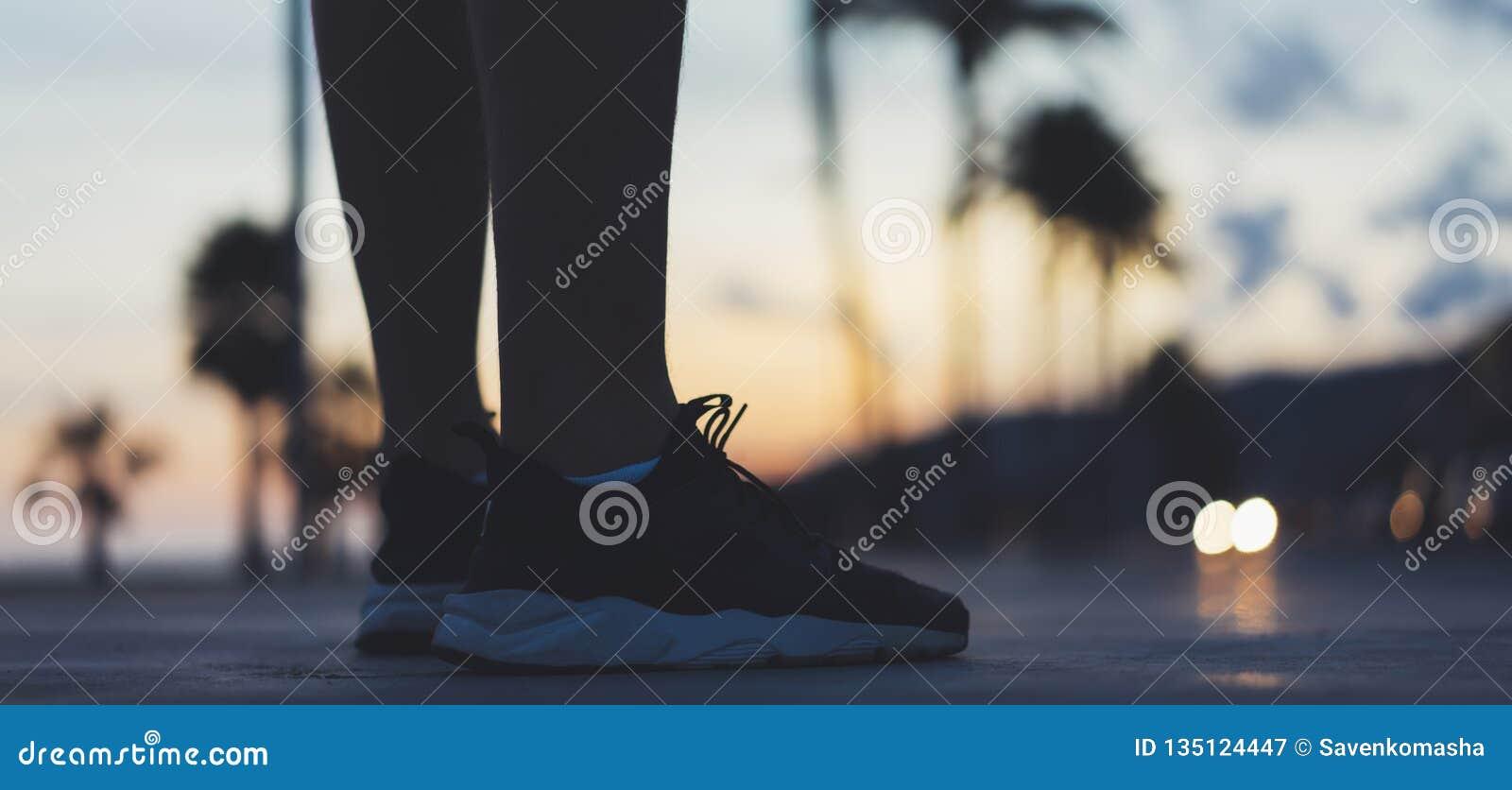 Мужские ноги с тапками закрывают вверх на заходе солнца предпосылки или природе на открытом воздухе, марафоне восхода солнца чело