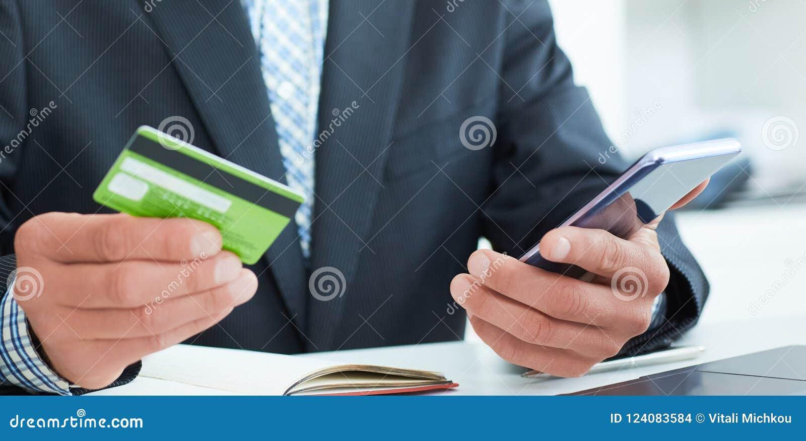 Мужские руки держа умные телефон и кредитную карточку на офисе Дело, технология, получает наличными свободно и концепция людей ин