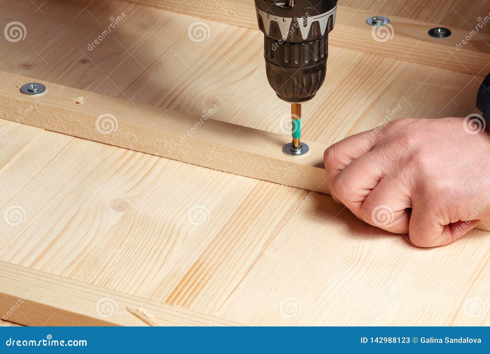 Мужские руки привинчивают деревянные блоки к доскам с отверткой