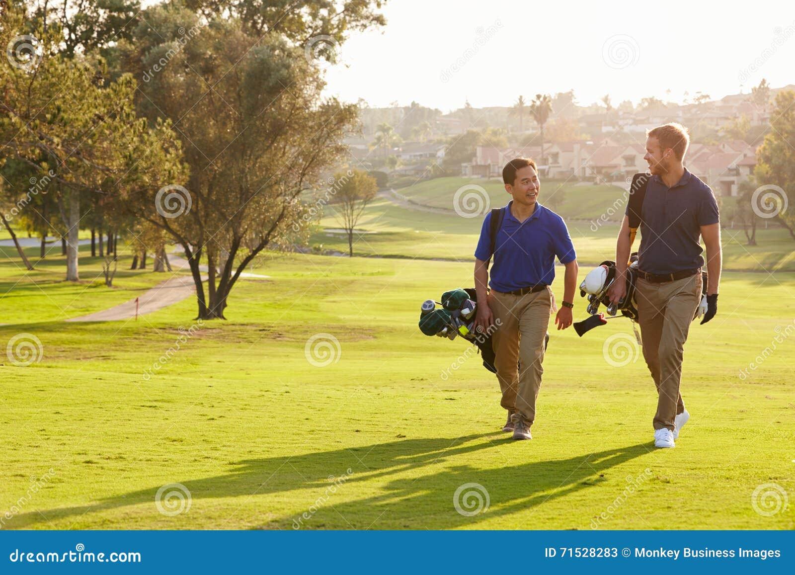 2 мужских игрока в гольф идя вдоль сумок нося прохода