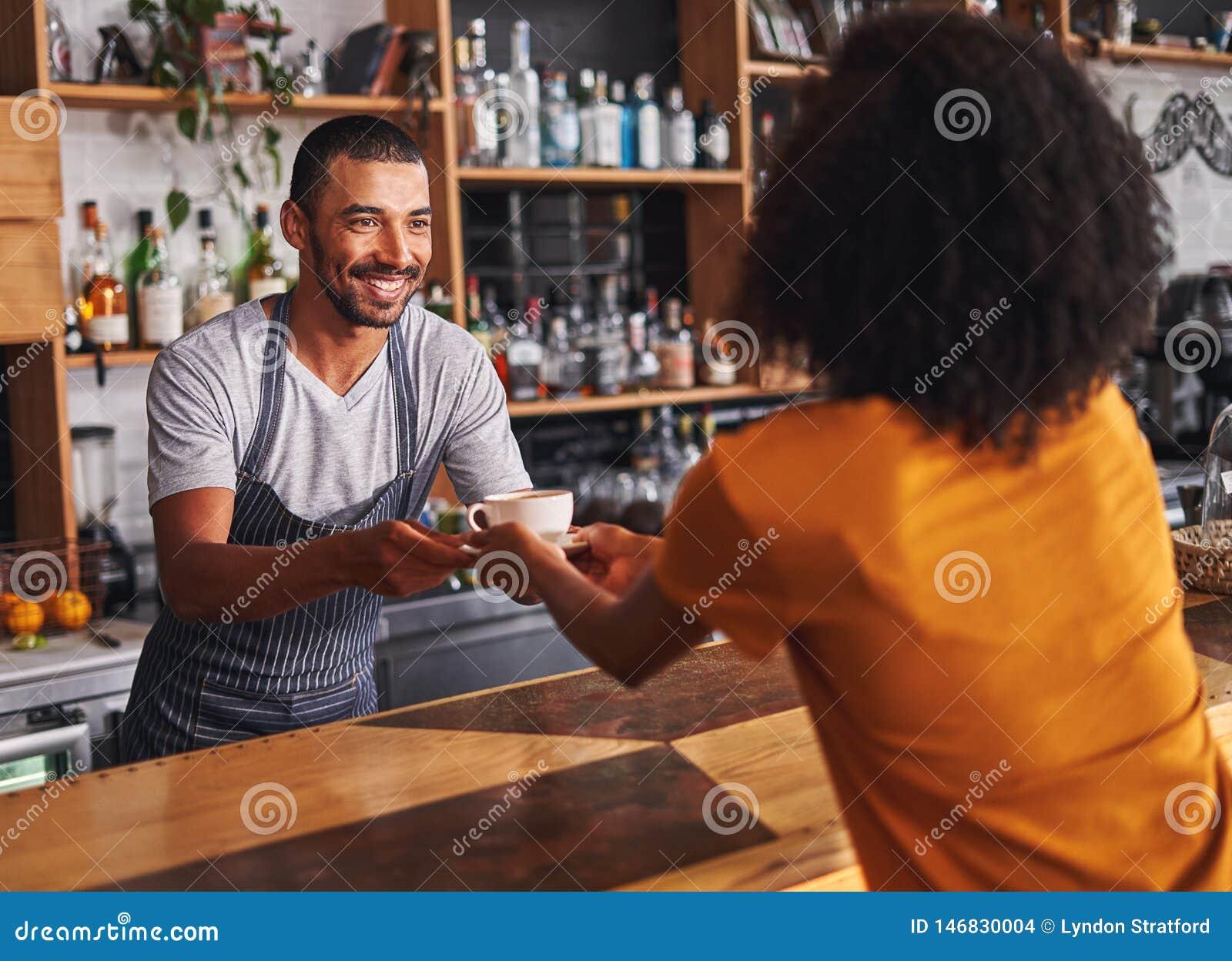 Мужское barista служит кофейная чашка к женскому клиенту в кафе