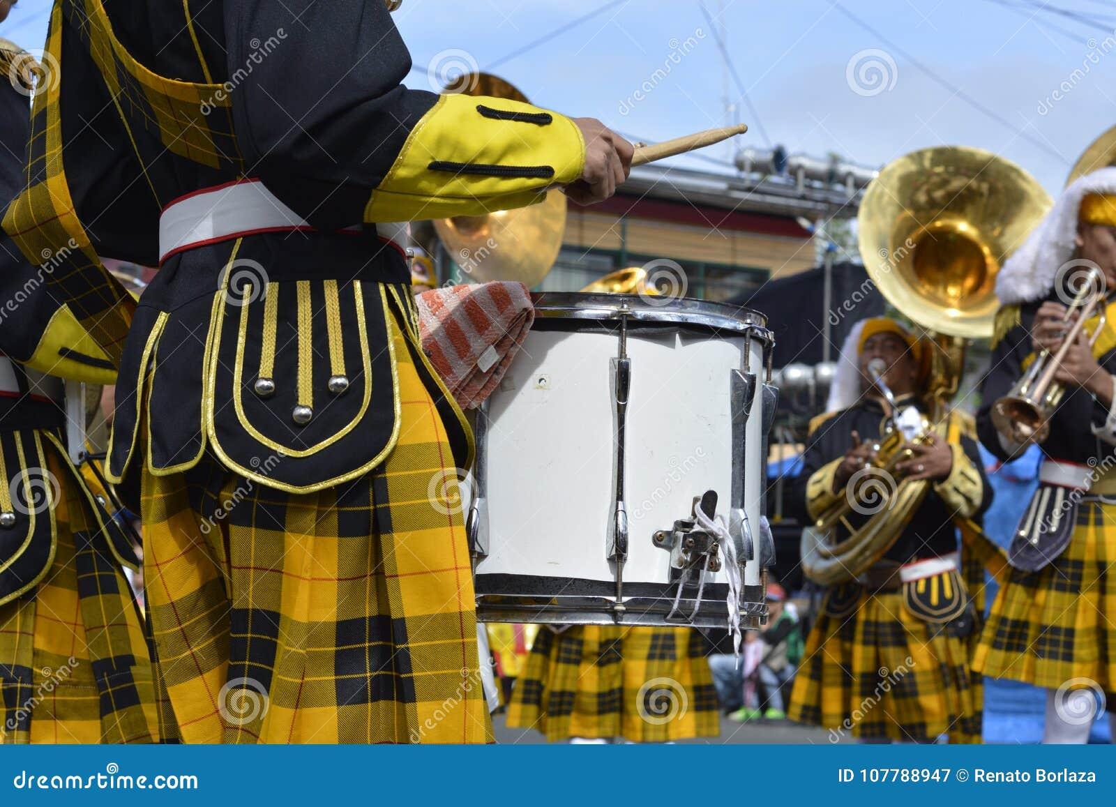 Мужской барабанчик игры члена банды на выставке улицы во время ежегодной выставки духового оркестра