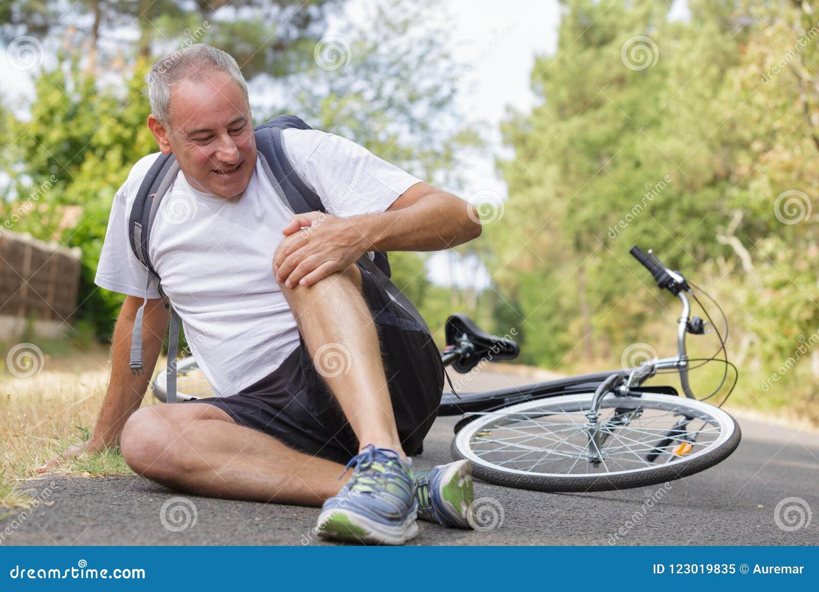 Мужской велосипедист получая раненый после аварии велосипеда