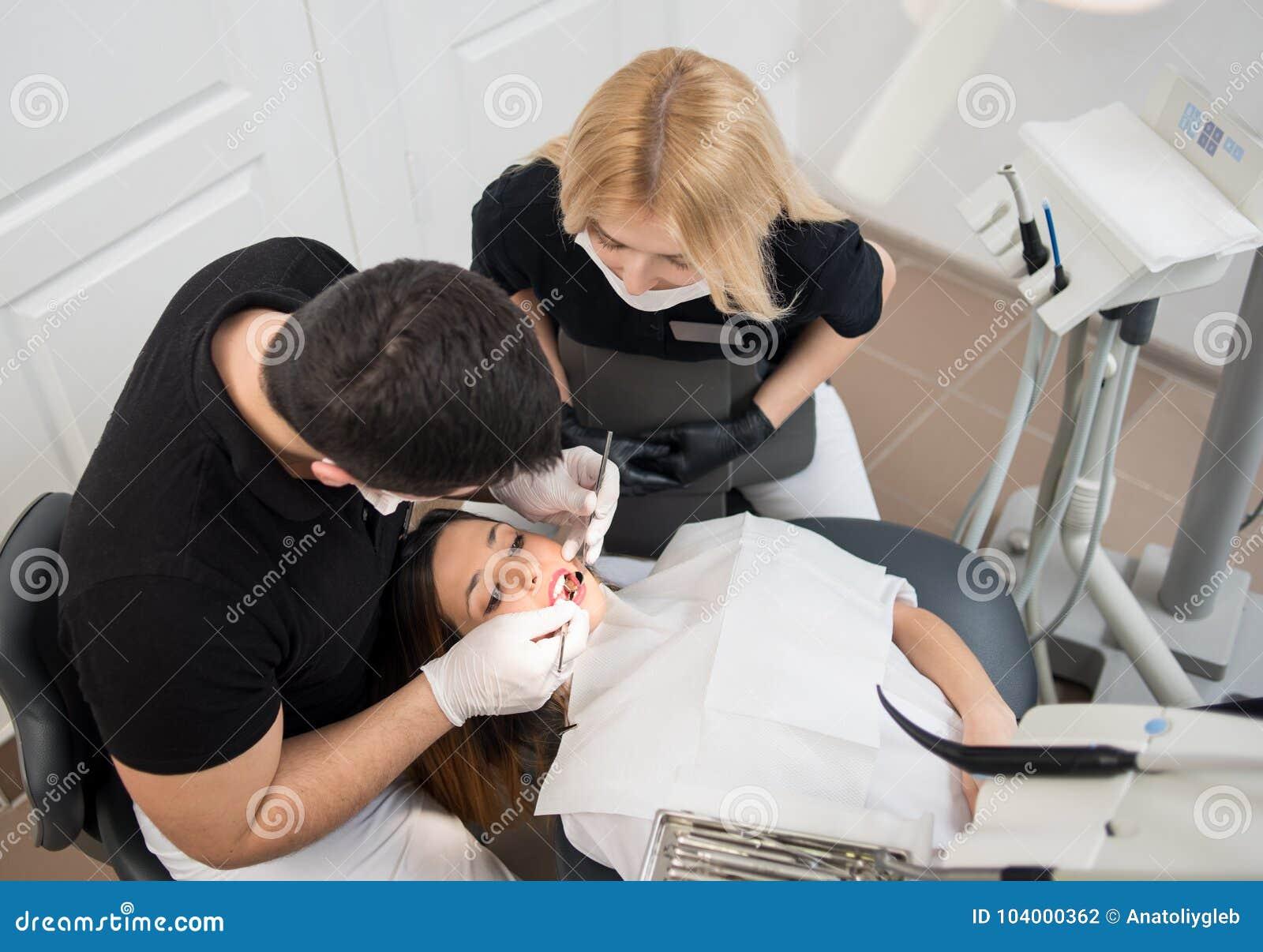 Мужской дантист и женский ассистент обрабатывая терпеливые зубы с зубоврачебными инструментами - отразите и прозондируйте на зубо