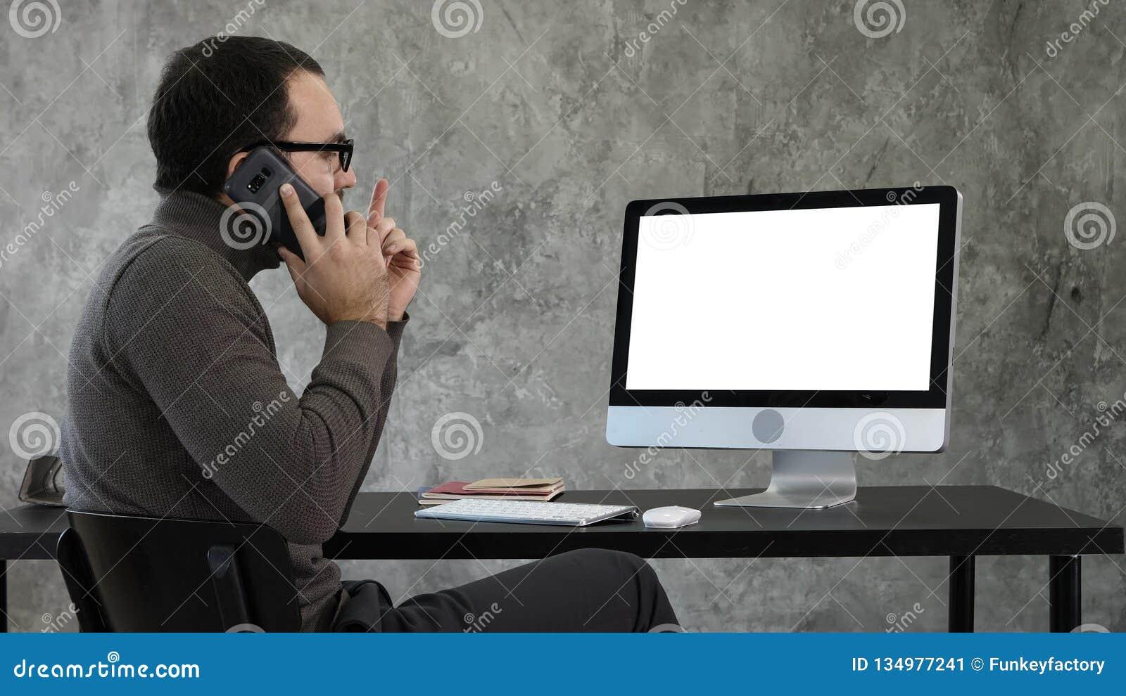 Мужской дизайнер работая на компьютере в современном офисе Он говорит на телефоне и смотреть на что на экране