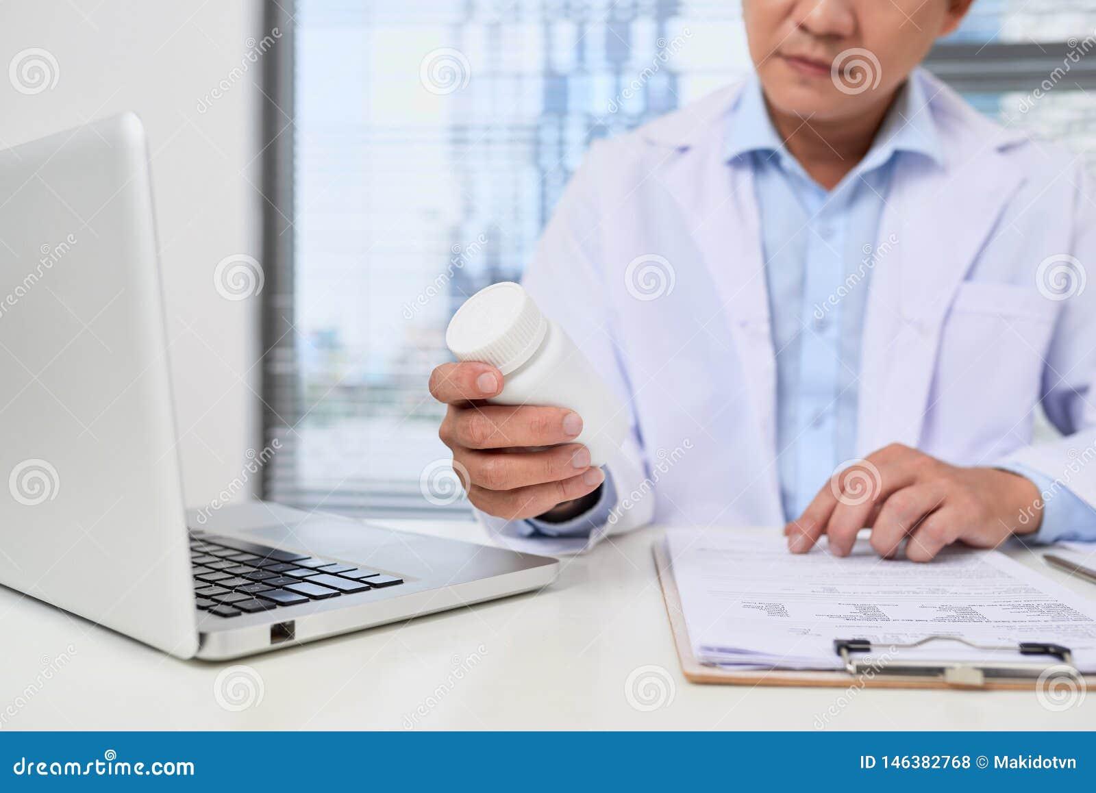 Мужской доктор держа коробку таблеток в медицинском офисе
