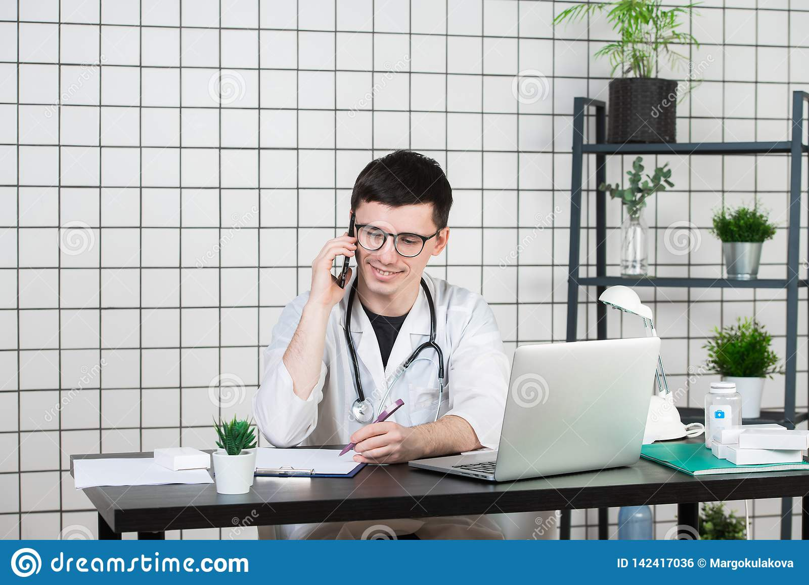 Мужской доктор используя телефон пока работающ на компьютере на таблице в клинике