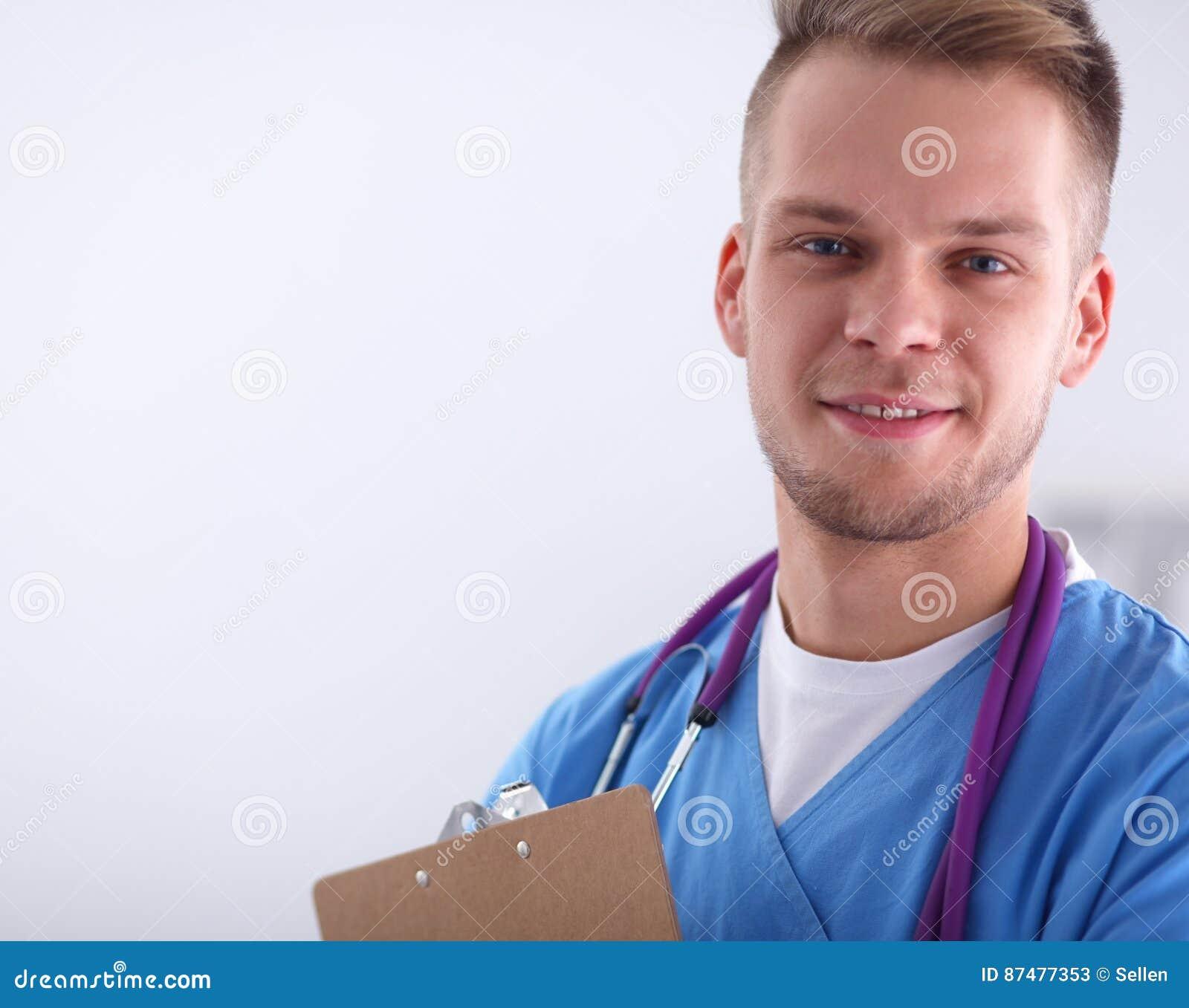 Мужской доктор стоя при папка, изолированная на белой предпосылке