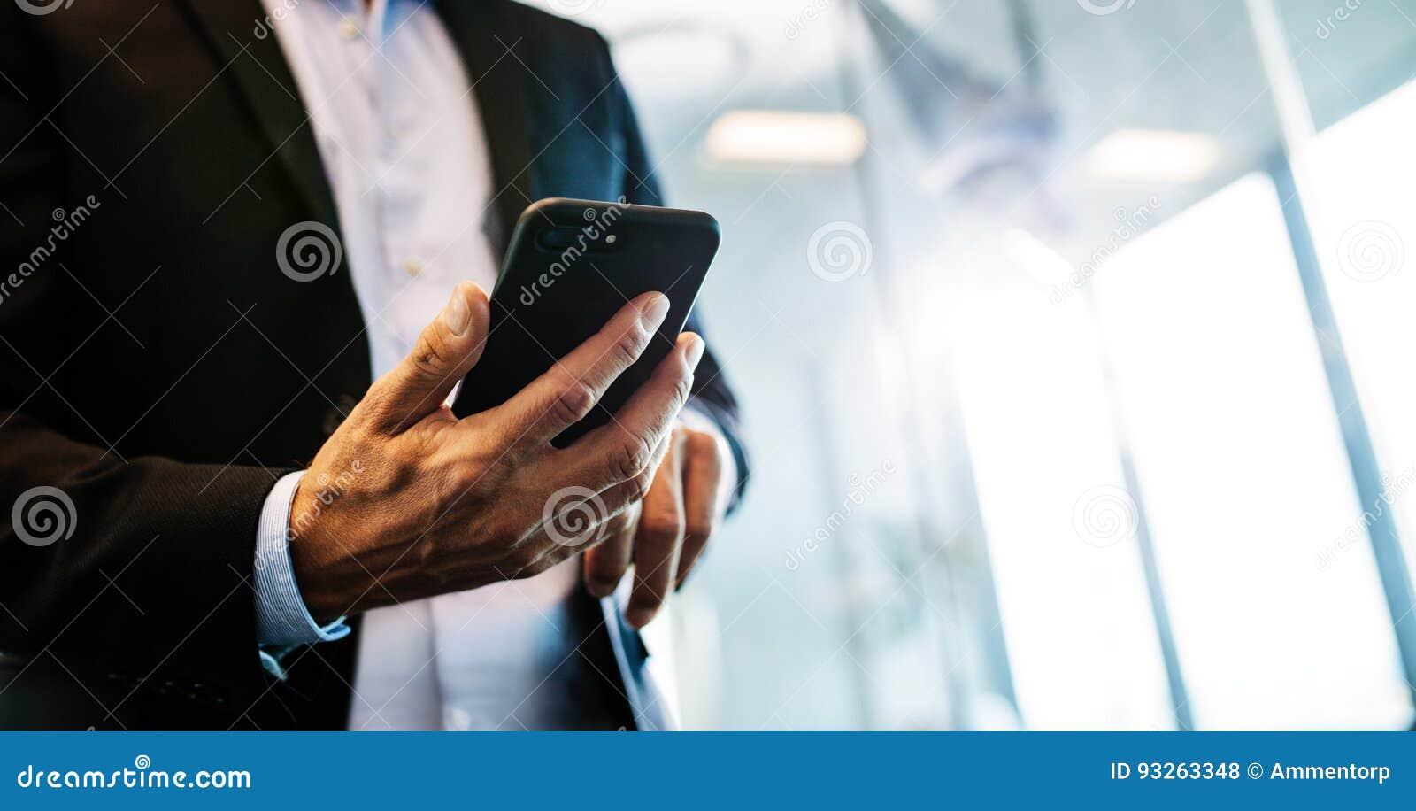 Мужской предприниматель с мобильным телефоном в офисе