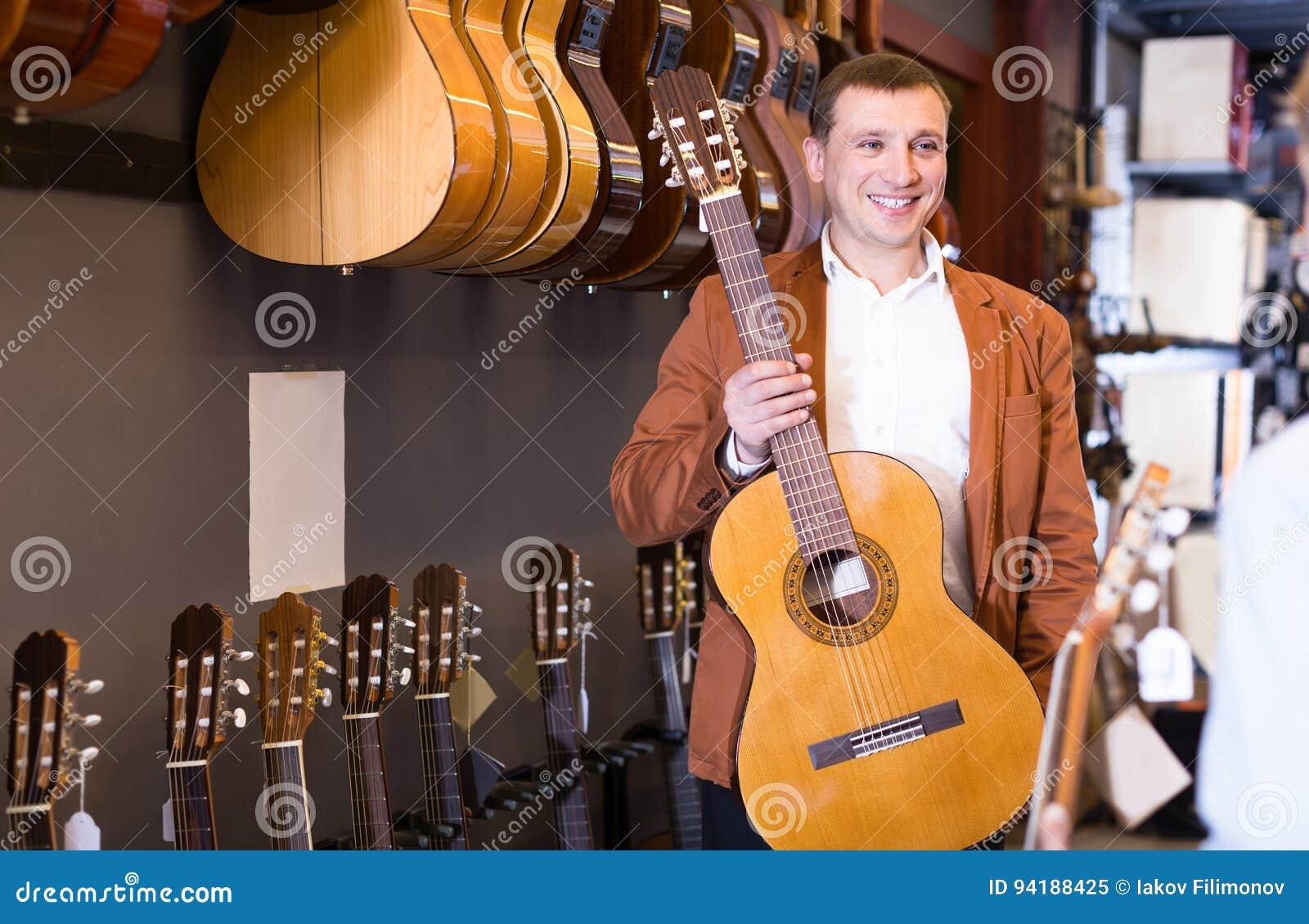 Мужской продавец показывая акустическую гитару к клиенту мальчика в музыкальном sho