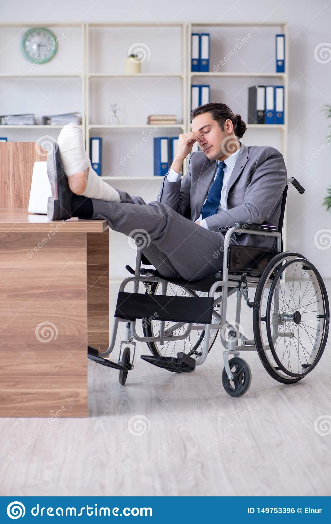 Мужской работник в кресло-коляске в офисе