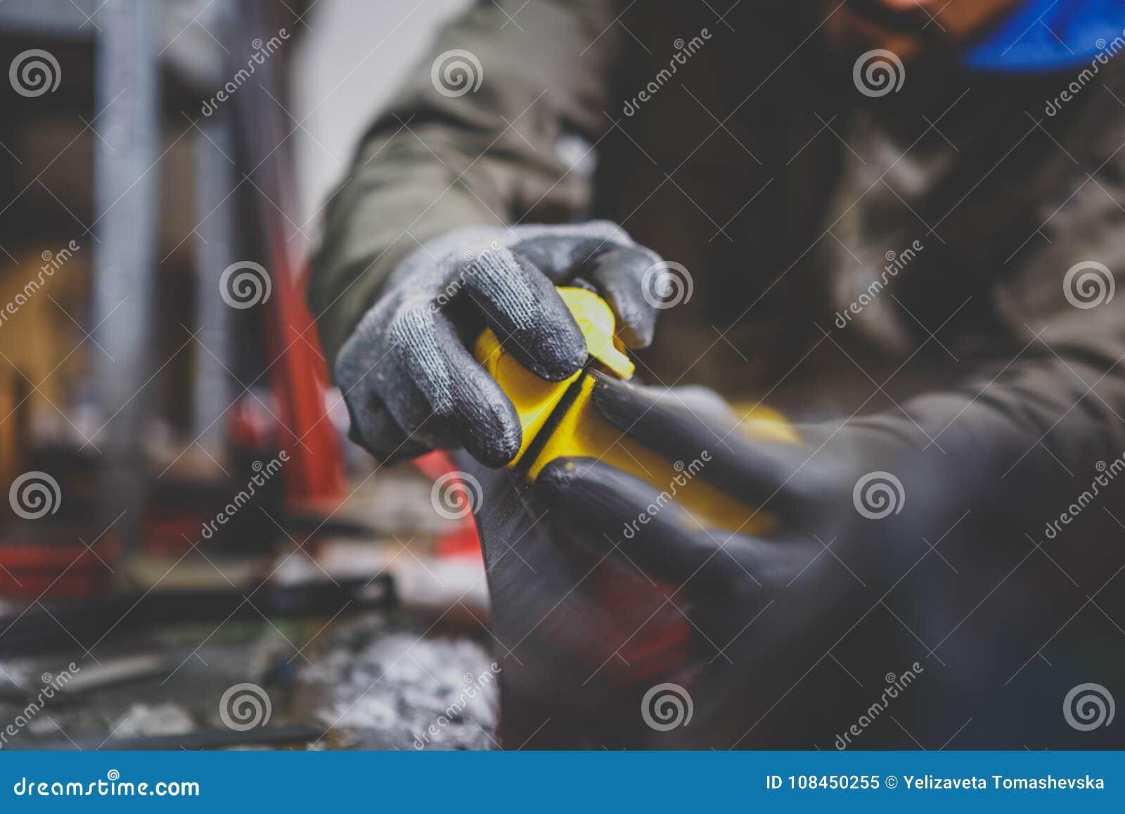 Мужской работник ремонтируя камень, край точить в мастерской обслуживания лыжи, сползая поверхности лыж точить выпушки mo