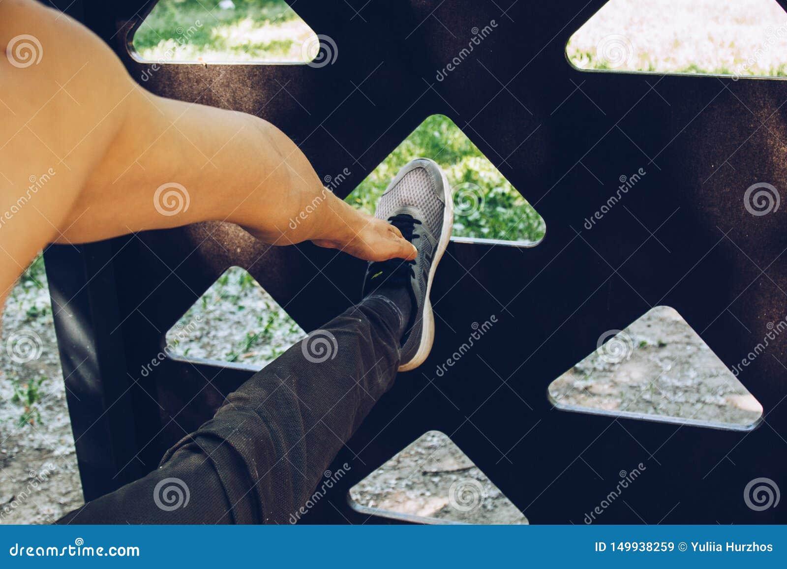 Мужской спортсмен в бежать положении ботинок спорт протягивает его ногу на спортивной площадке с лестницей металла простирания вр