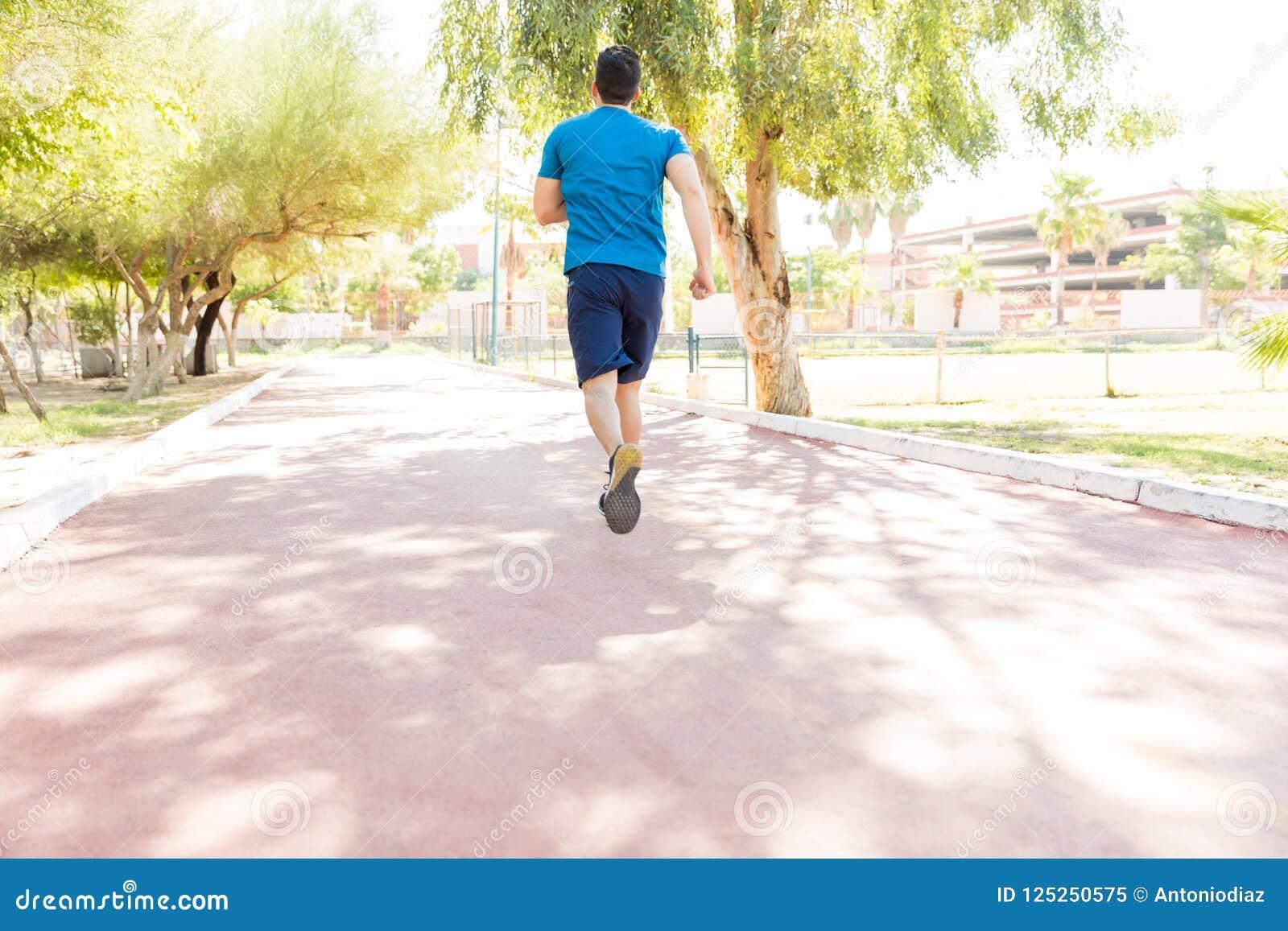 Мужской спортсмен Sprinting на дороге в парке