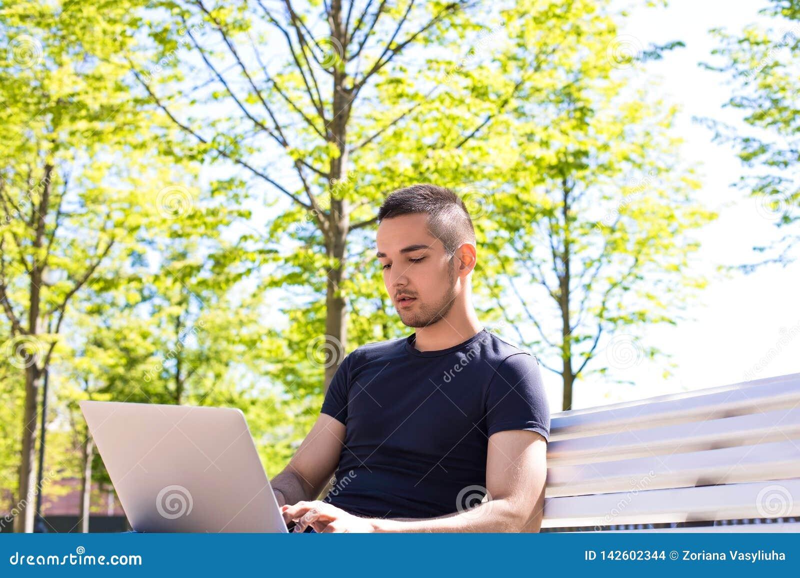 Мужской текст рекламируя писателя печатая для вебсайта на netbook, сидя outdoors