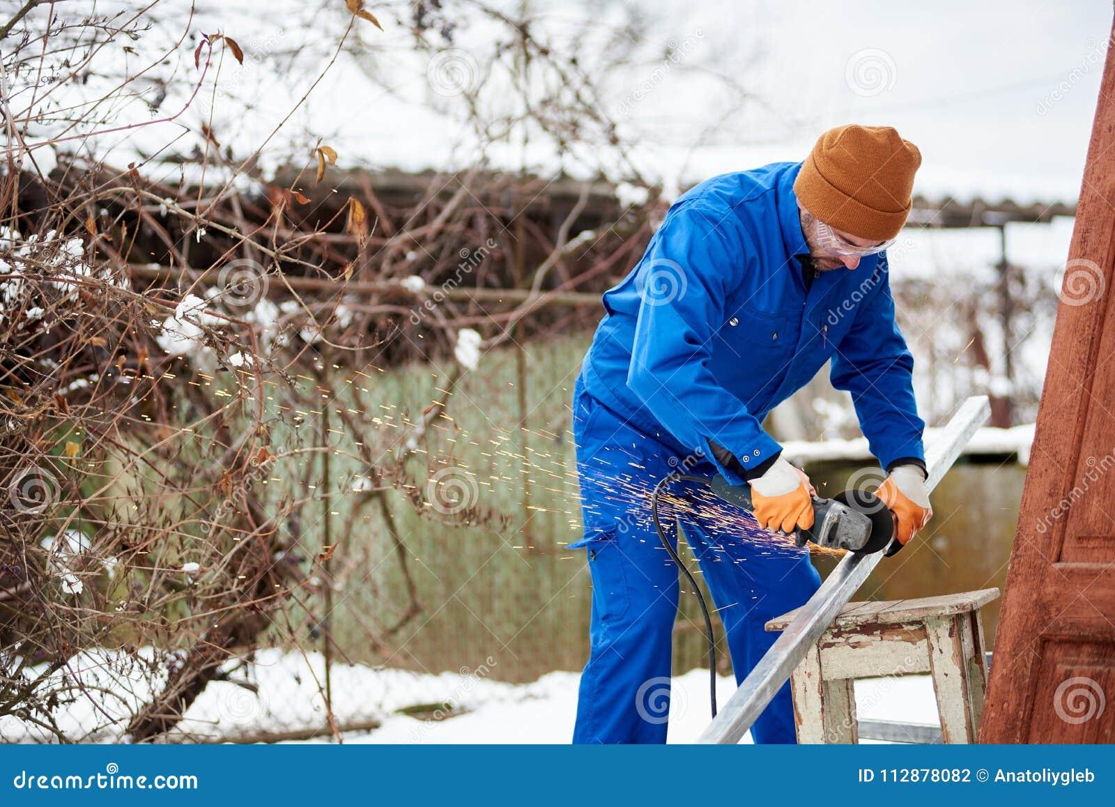 Мужской техник в голубом инструментальном металле костюма при режущий диск получая готовый установить фотовольтайческие панели со