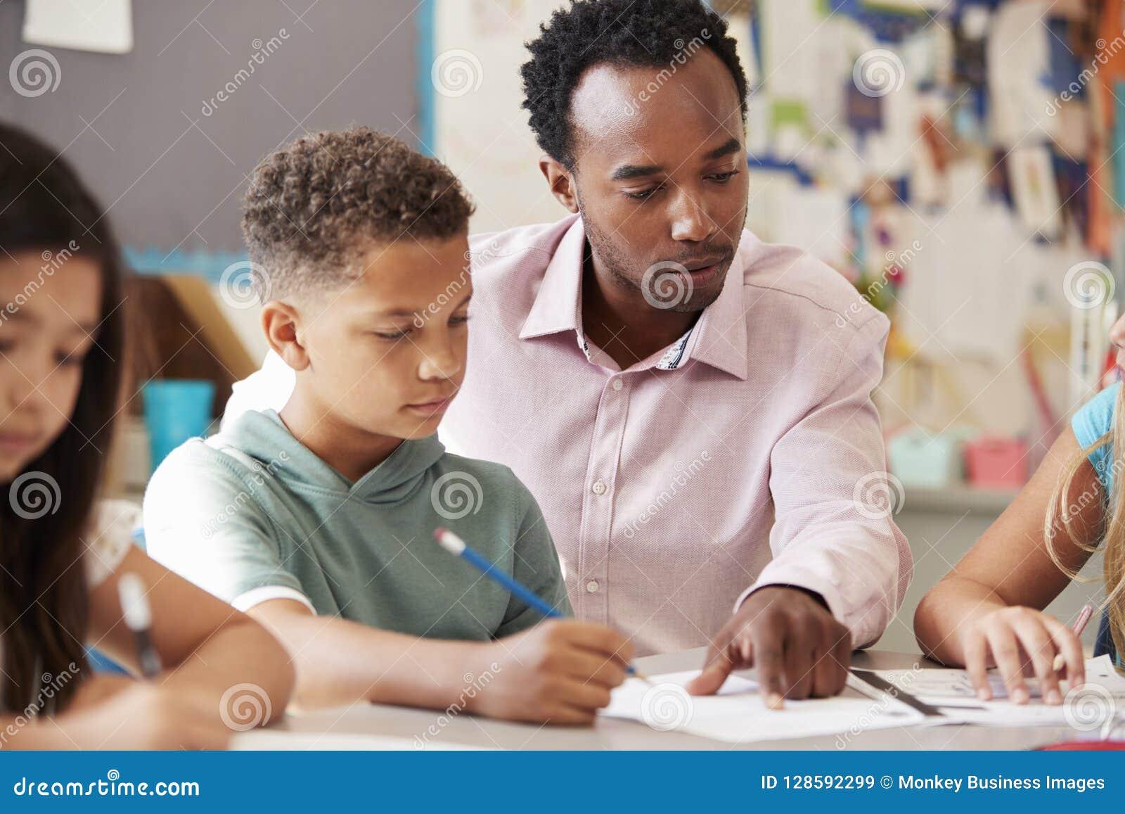 Мужской учитель работая с школьником на столе, конце вверх