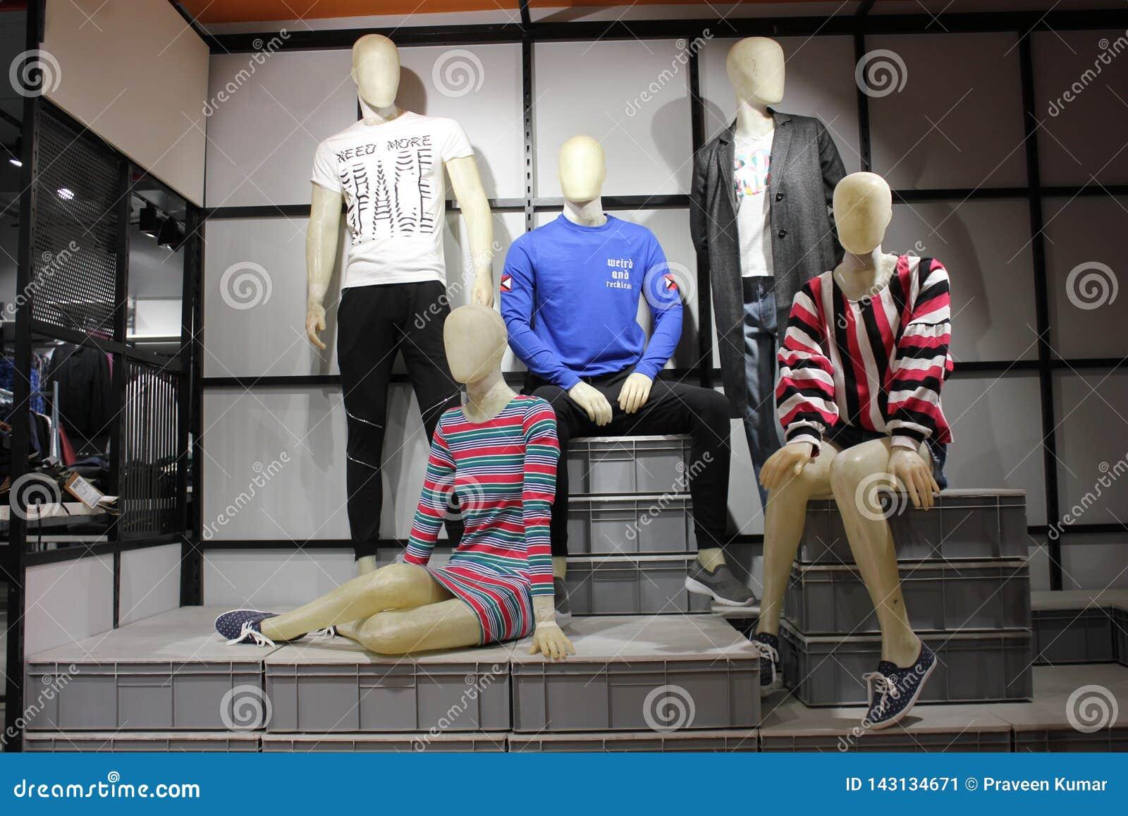 Мужчина и женские манекены в западной моде показанной в магазине одежды в торговом центре