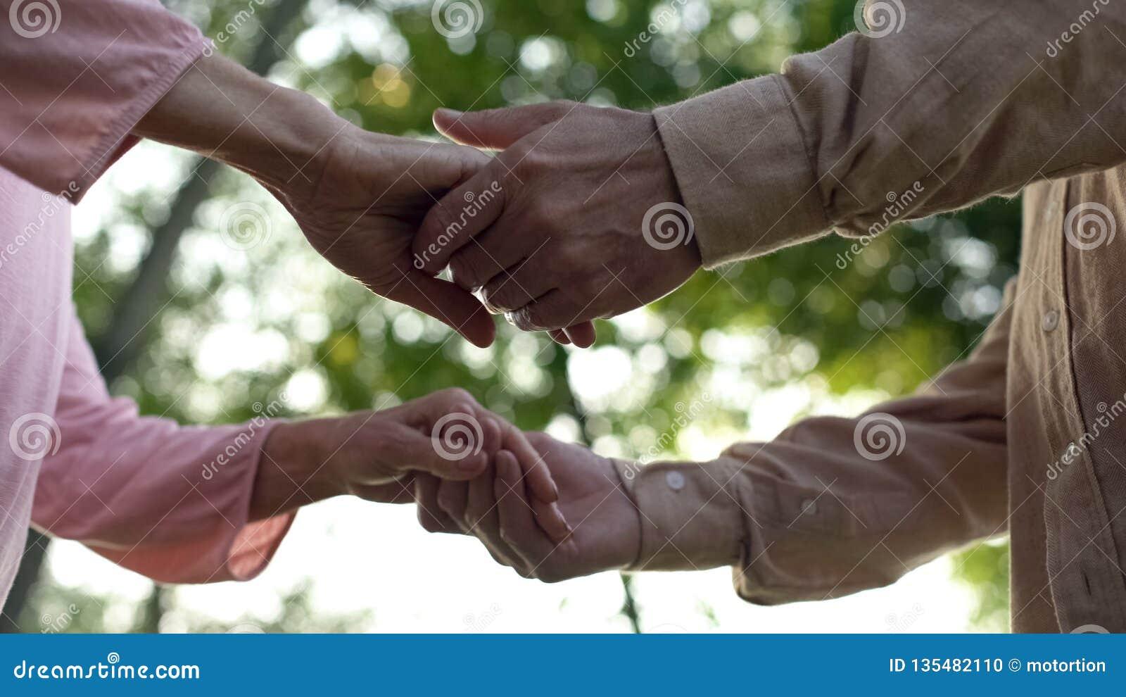 Мужчина и женские пенсионеры держа руки, романтичную дату на открытом воздухе, приглашение