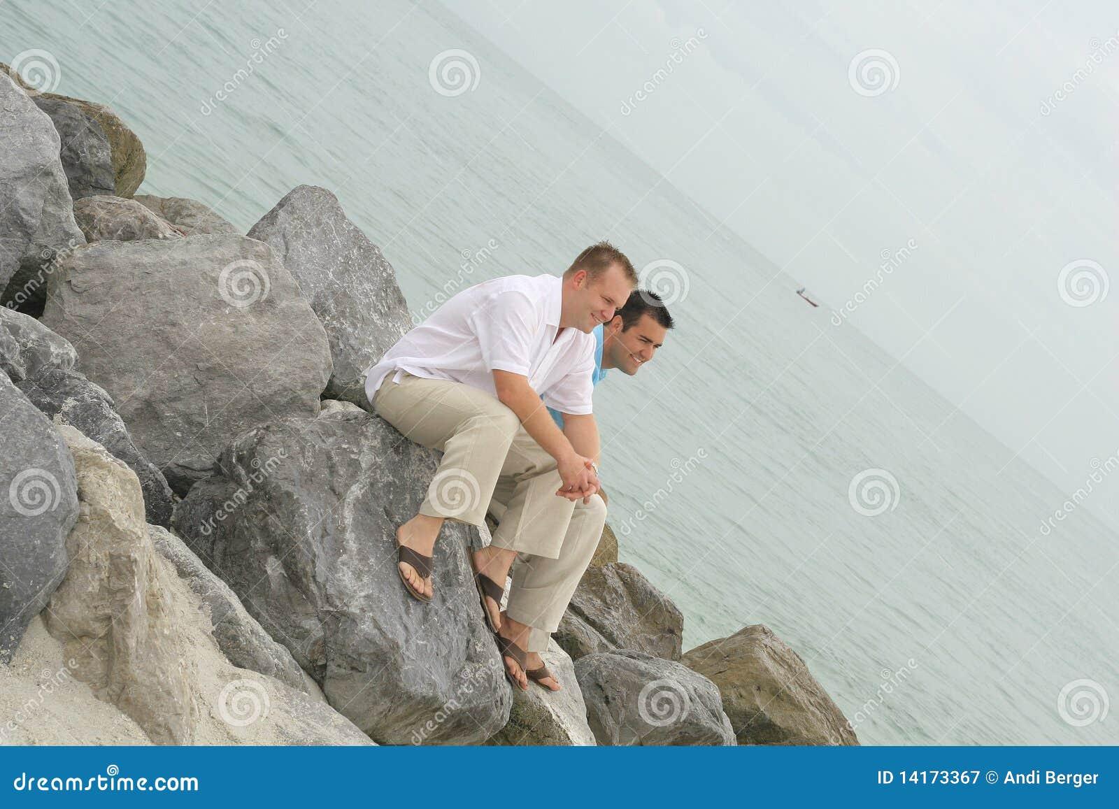 мужчина моделирует сидеть утесов