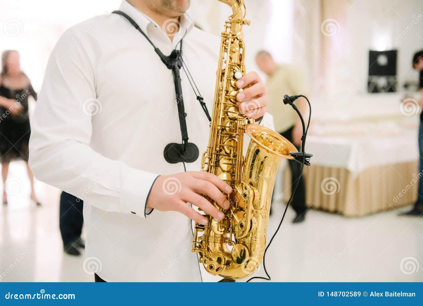 Музыкант играет конец-вверх саксофона внутри помещения Саксофонист играет саксофон на конце-вверх события