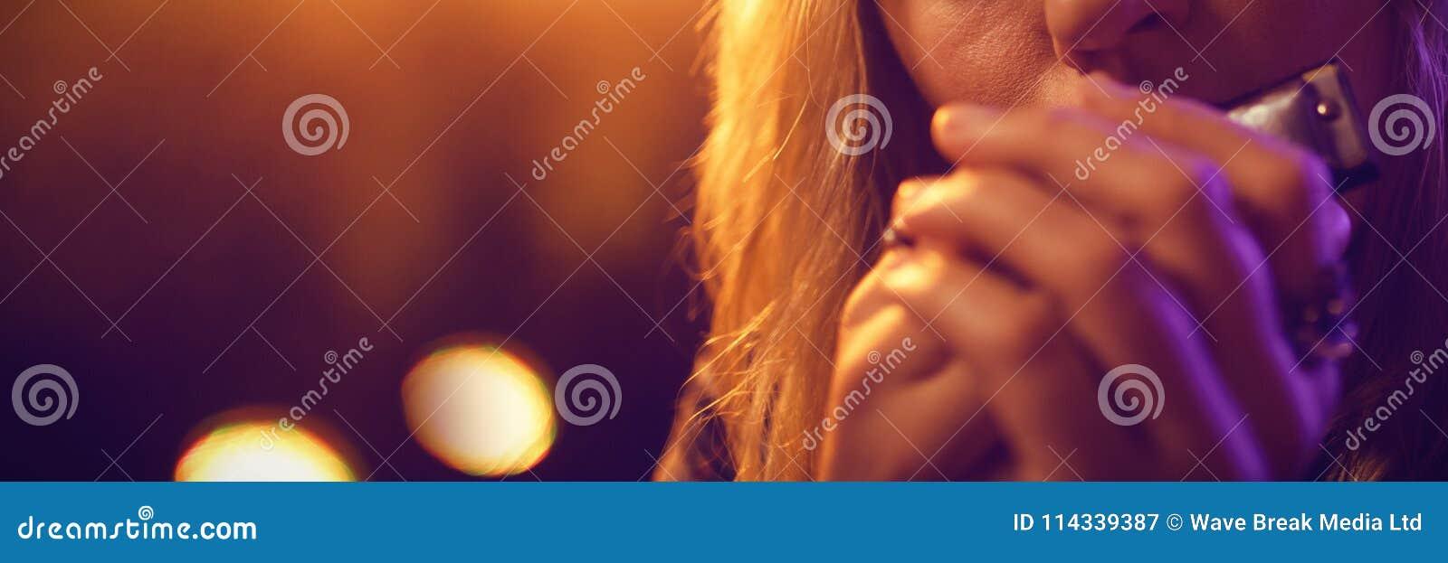 Музыкант играя губную гармонику в ночном клубе