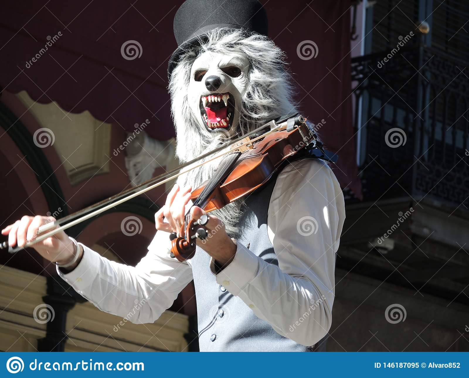 Музыкант с маской играя скрипку