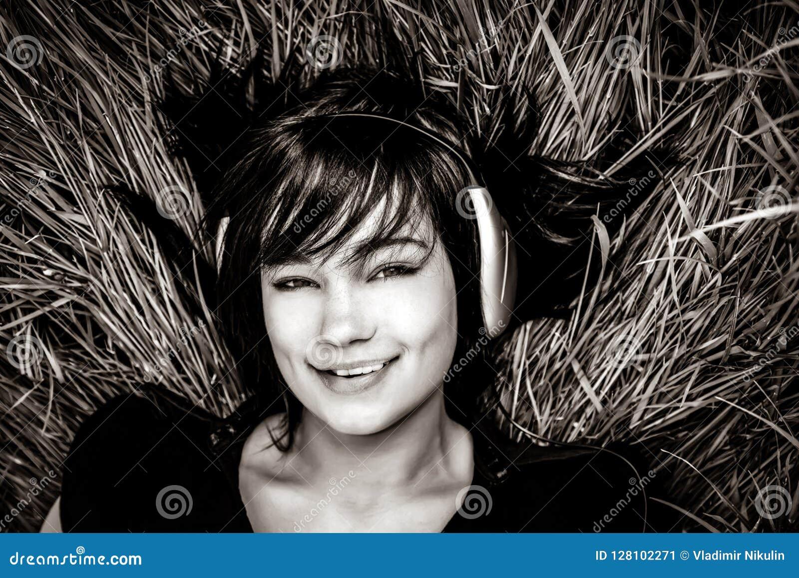 Музыка девушки брюнет слушая на траве