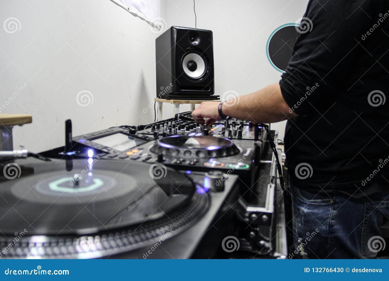 Музыка молодого парня играя и смешивая на регуляторе DJ
