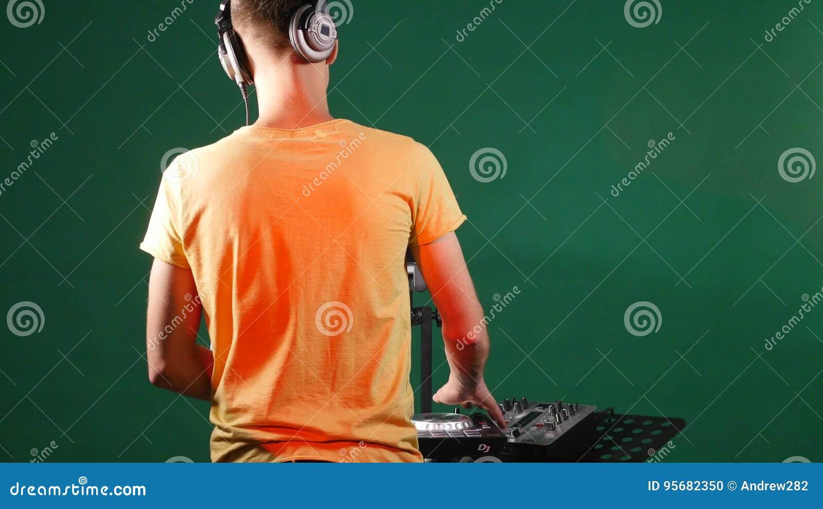 Музыка стоя на его палубе, танец dj смешивая в его наушнике, от задней части
