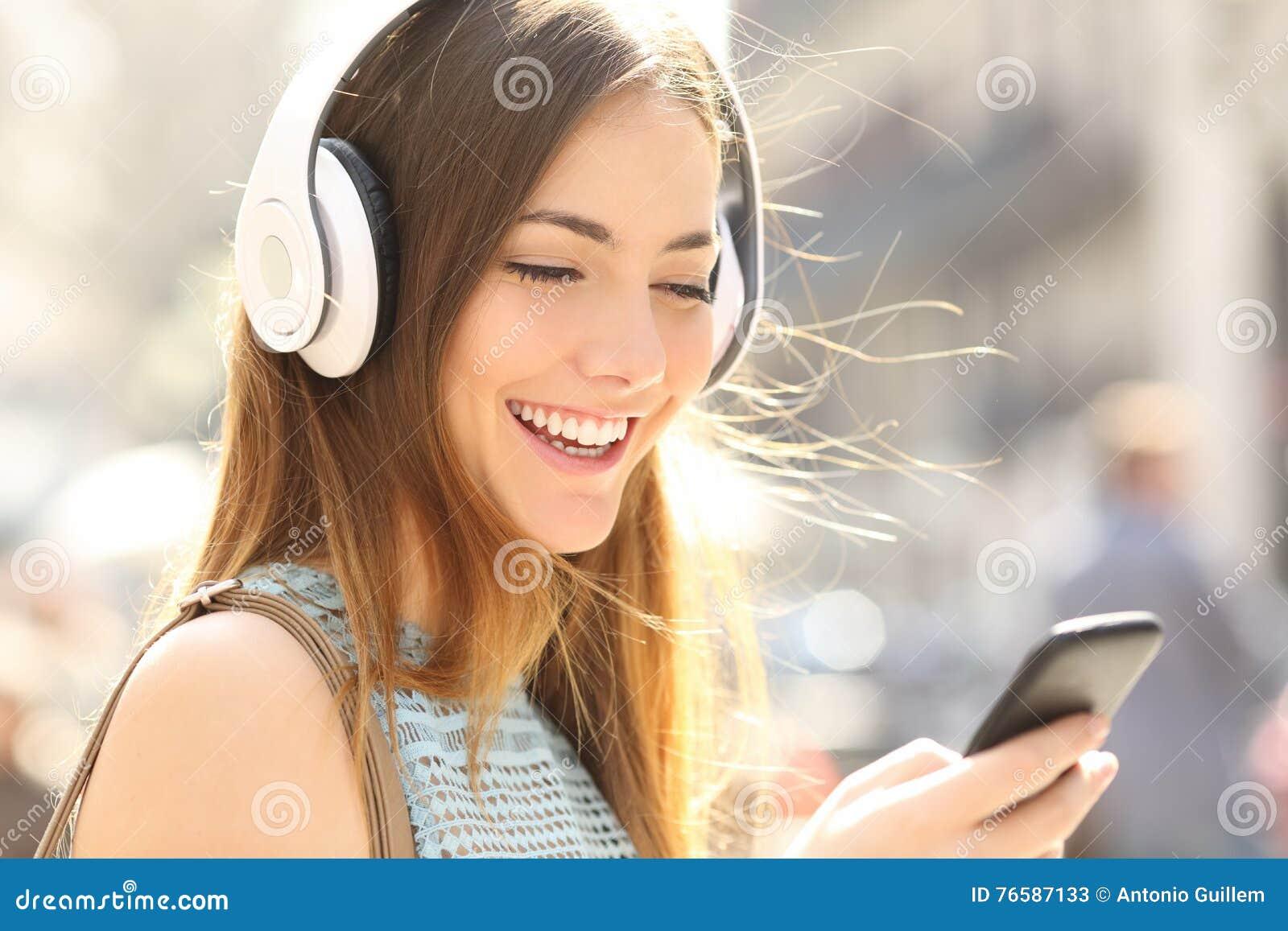 Музыка счастливой девушки слушая с наушниками