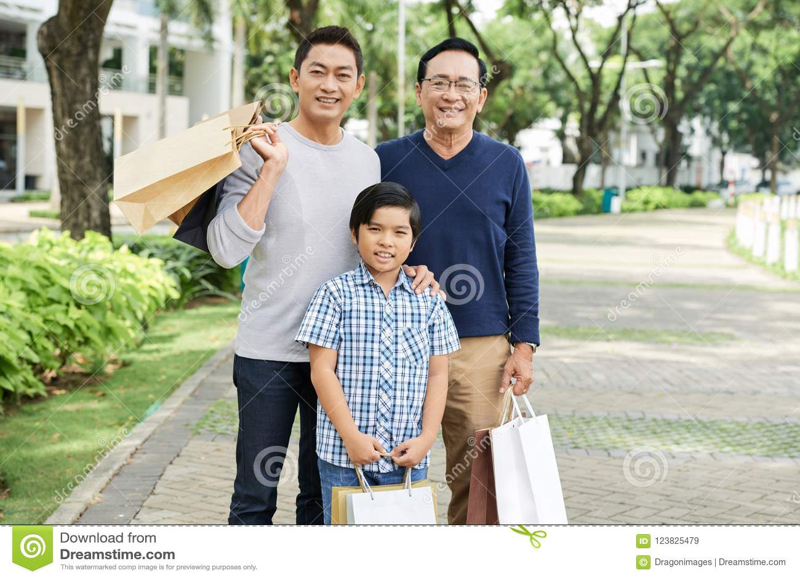 Мульти-поколенческая азиатская семья с бумажными сумками