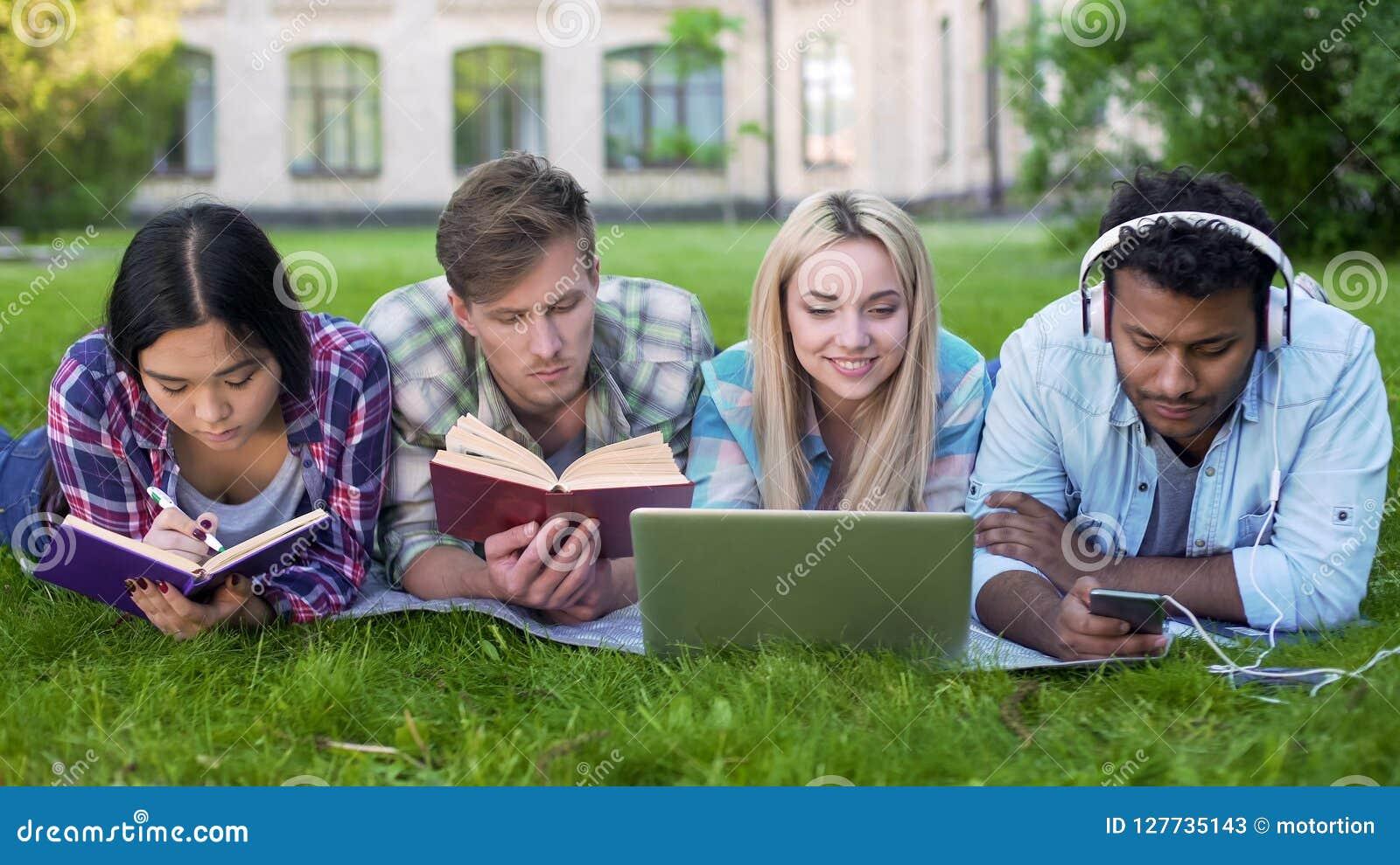 Мульти-этнические люди и женщины делая домашнюю работу на траве на кампусе, высшее образование