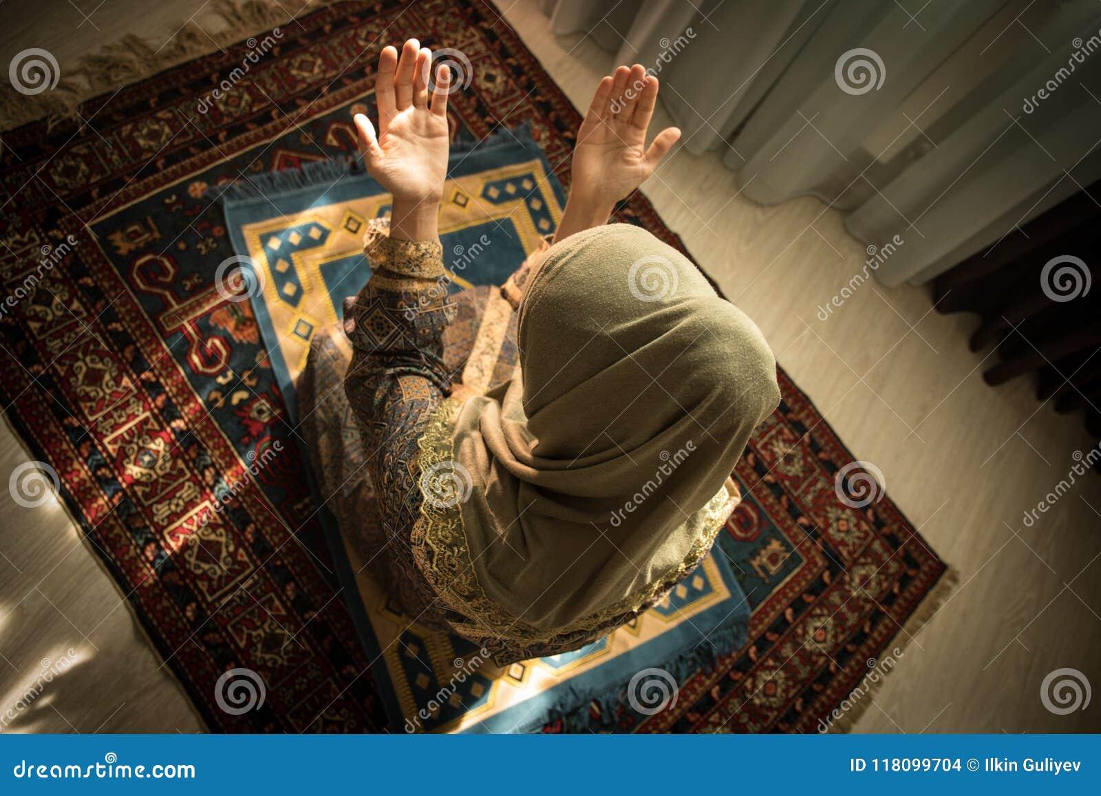 Мусульманская женщина моля для бога Аллаха мусульманского на комнате около окна Руки мусульманской женщины на ковре моля в традиц