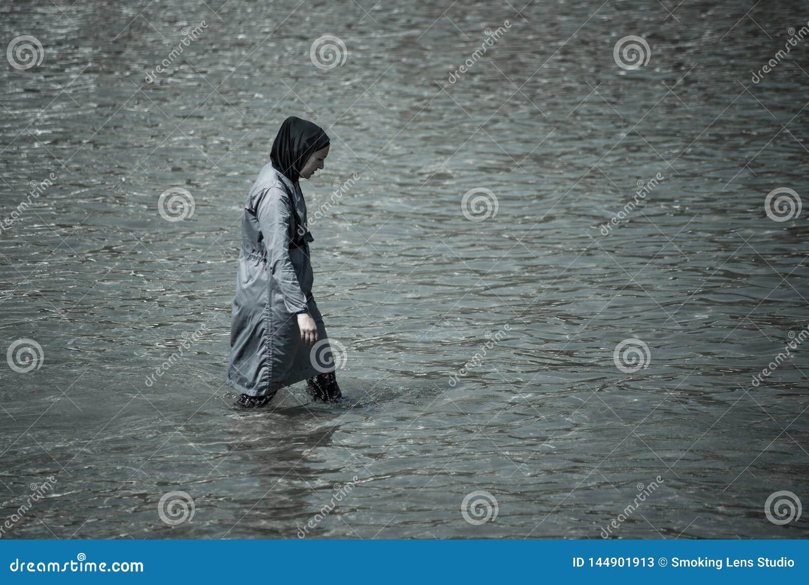 Мусульманская женщина принимая заплыв в море вполне покрытом с одеждами