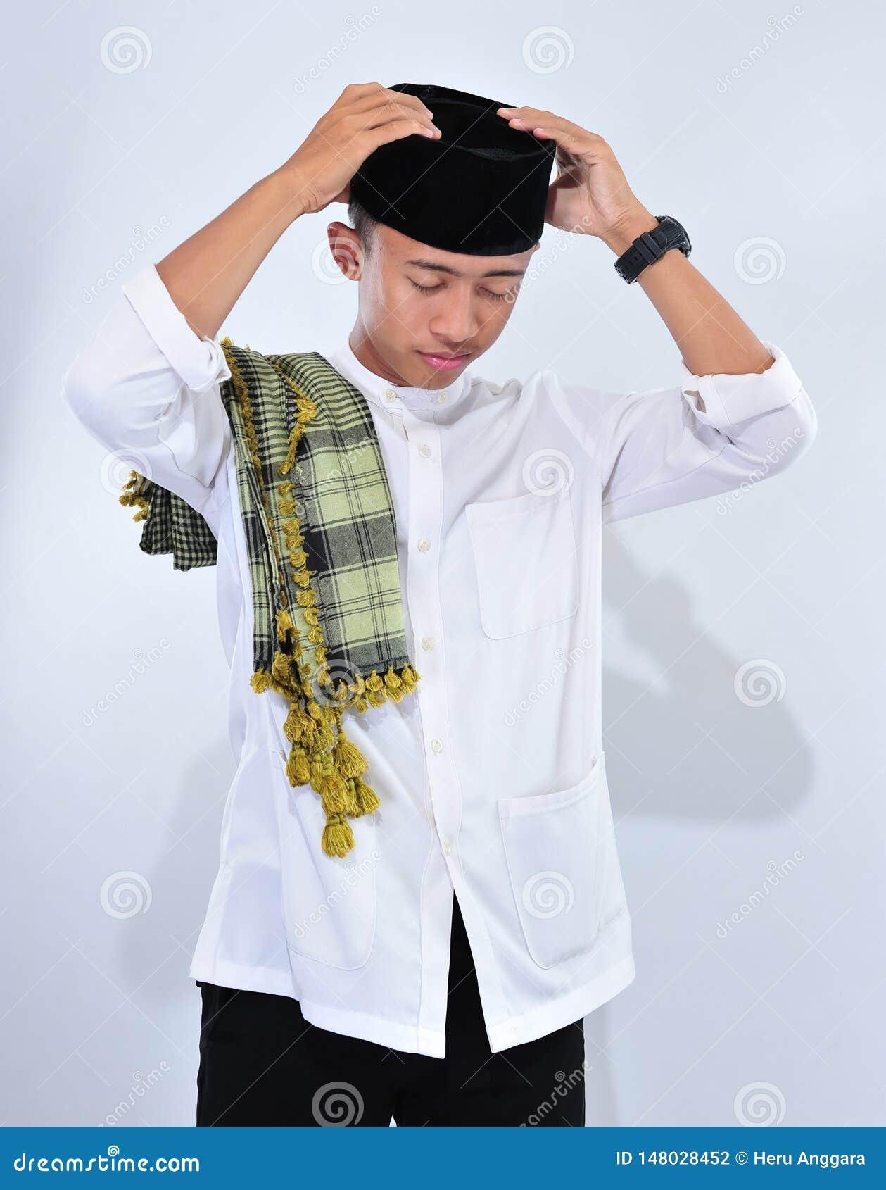 Мусульманский человек носит чашку черепа и белые традиционные одежды в ied торжестве mubarak