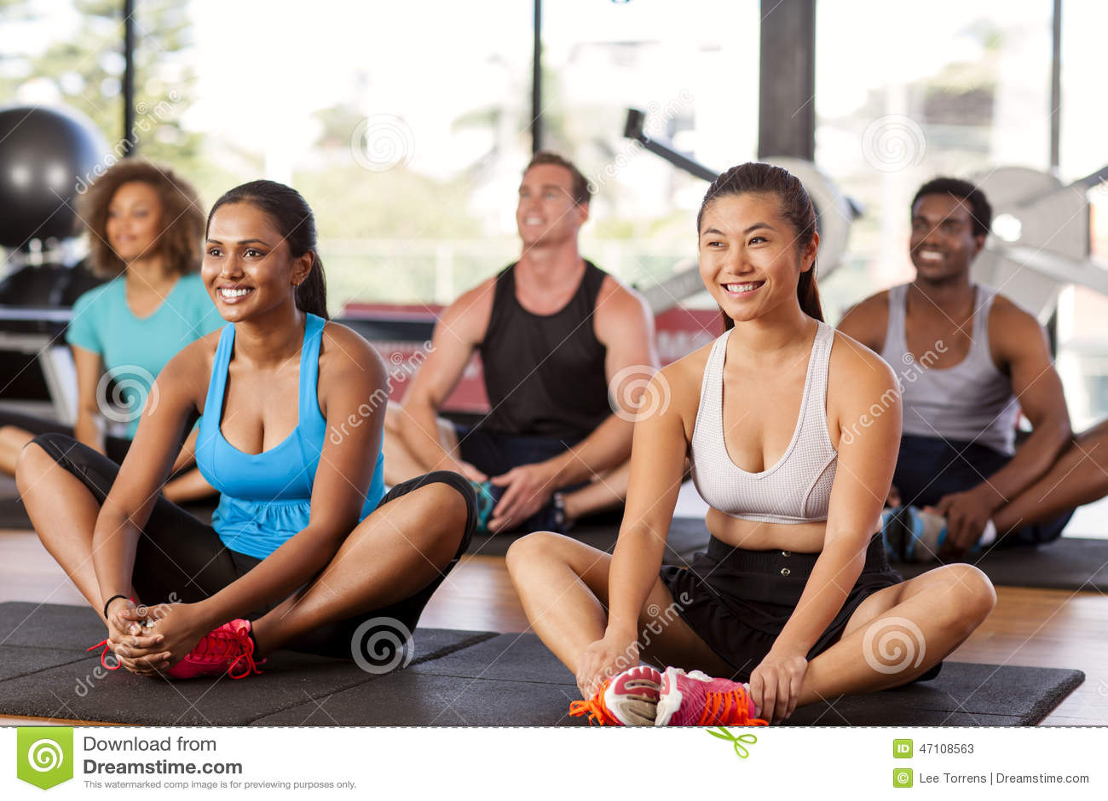 Мульти-этническая группа протягивая в спортзале