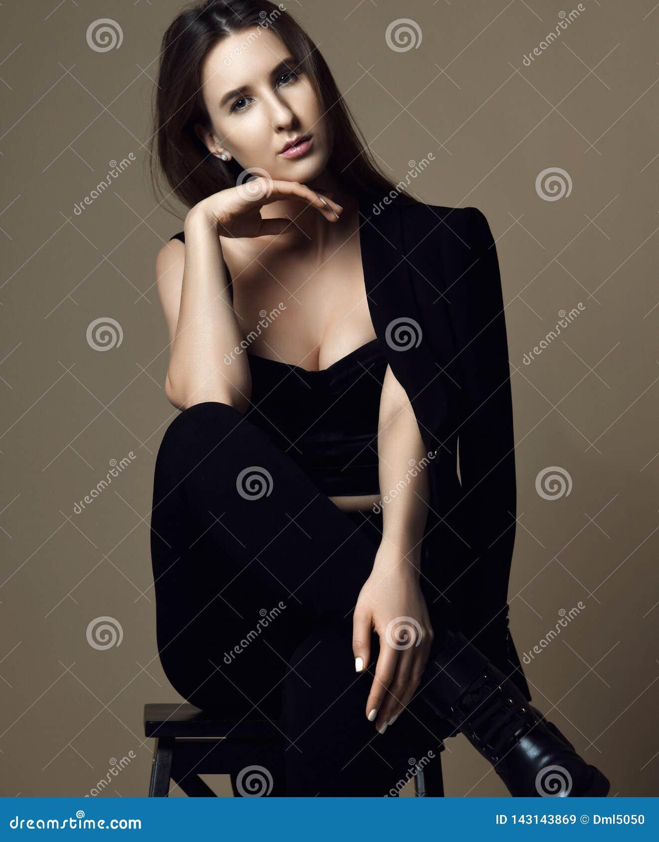 Мысль молодой красивой девушки хипстера сидя сексуальная в коричневых куртке и нижнем белье весны