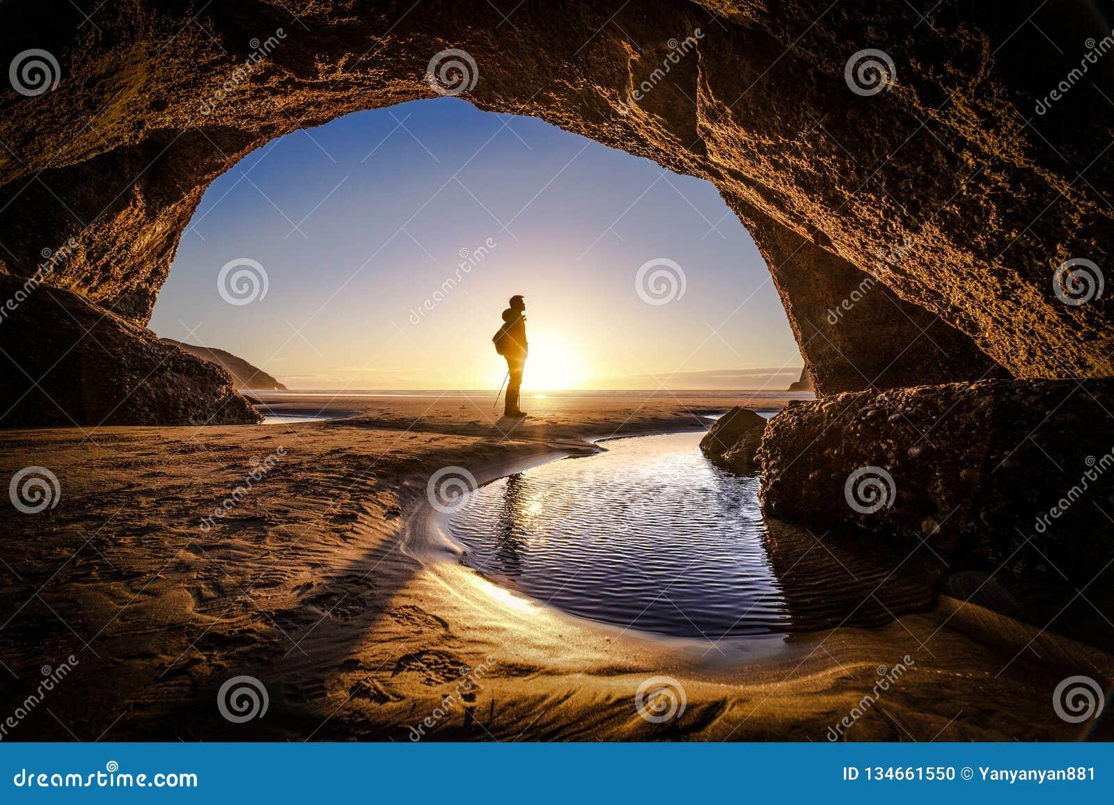Мысль человека глубокая внутри пещеры пляжа wharariki в Новой Зеландии