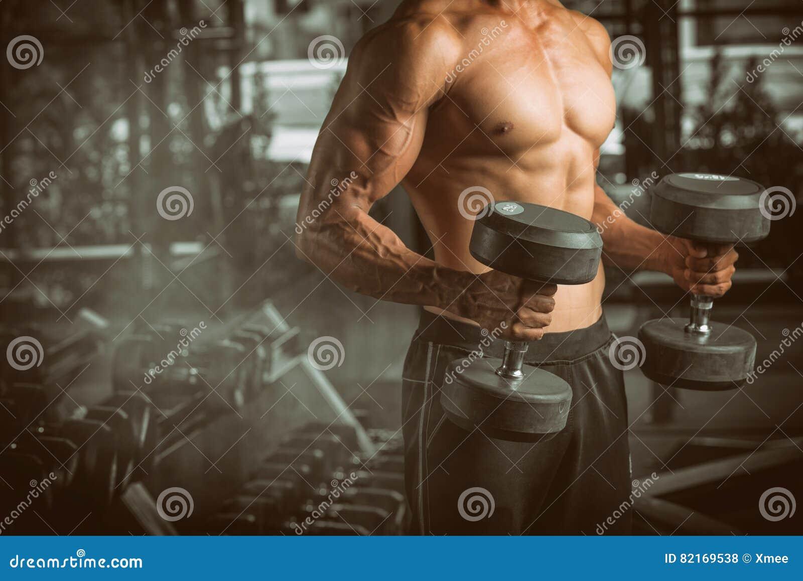 Мышечные весы молодого человека поднимаясь на фитнес-центре