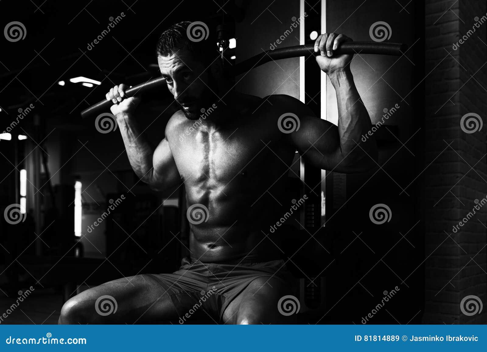 Мышечный человек делая тяжеловесную тренировку для задней части