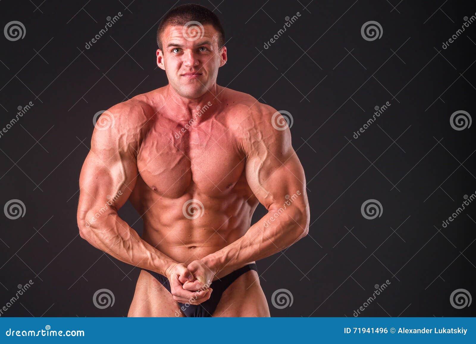 Мышечный человек на темной предпосылке