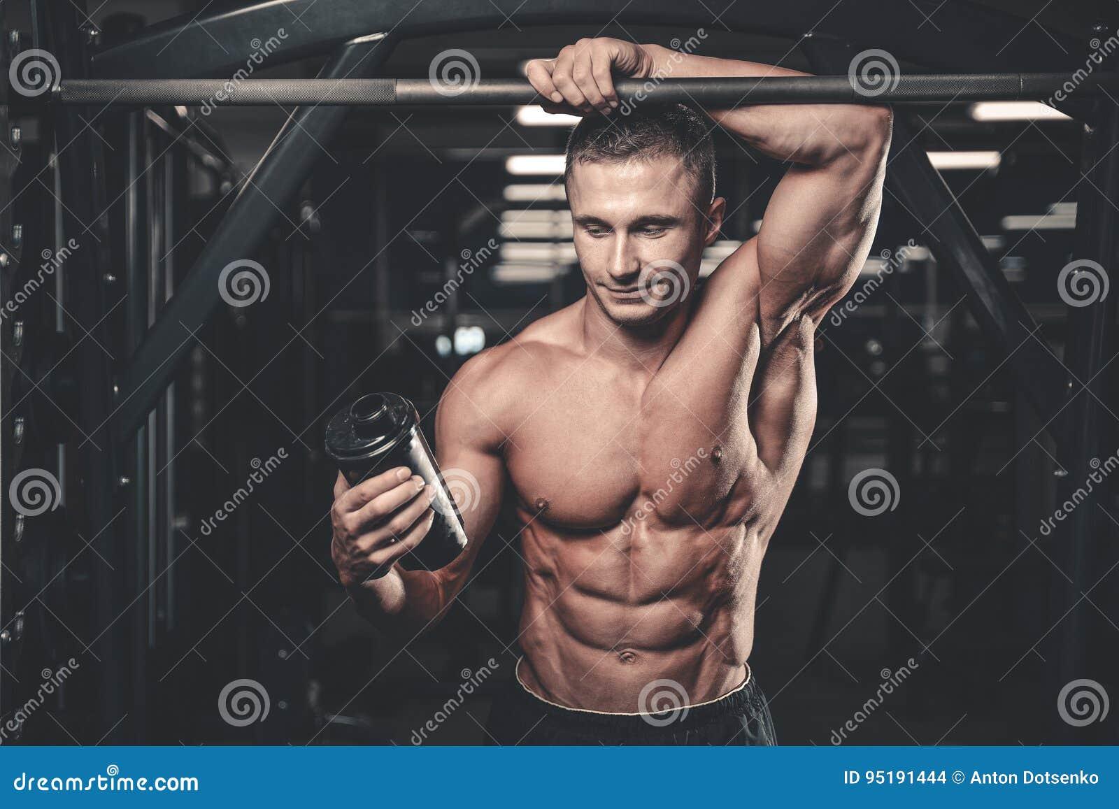 Мышечный человек отдыхая после тренировки и выпивая от шейкера