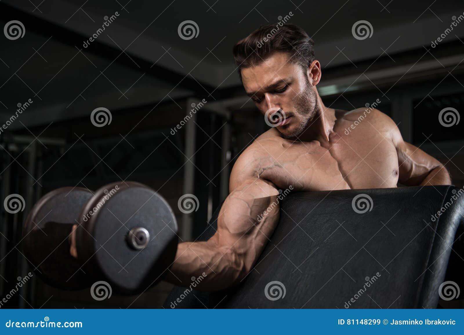 Мышечный человек работая бицепс с гантелью