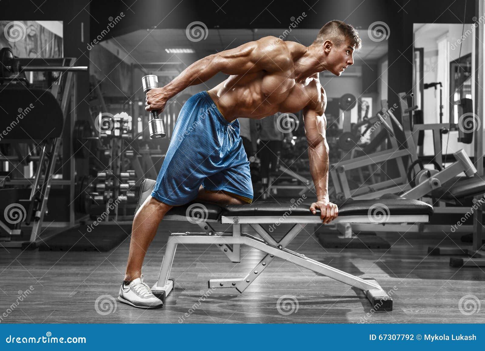Мышечный человек разрабатывая в спортзале делая тренировки с гантелями на трицепсах, сильном мужском нагом abs торса