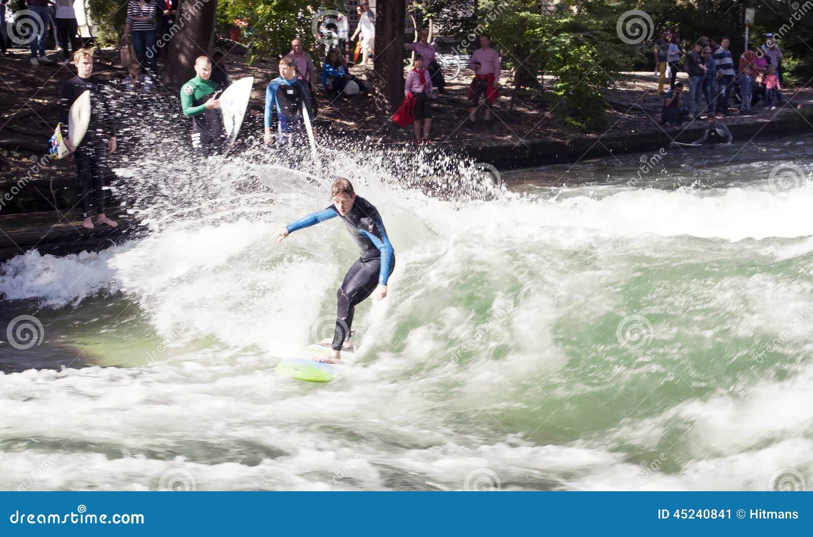 МЮНХЕН, ГЕРМАНИЯ - 1-ОЕ НОЯБРЯ: Серферы тренируют на искусственной волне о 1 метре высокий в реке Eisbach в английском саде